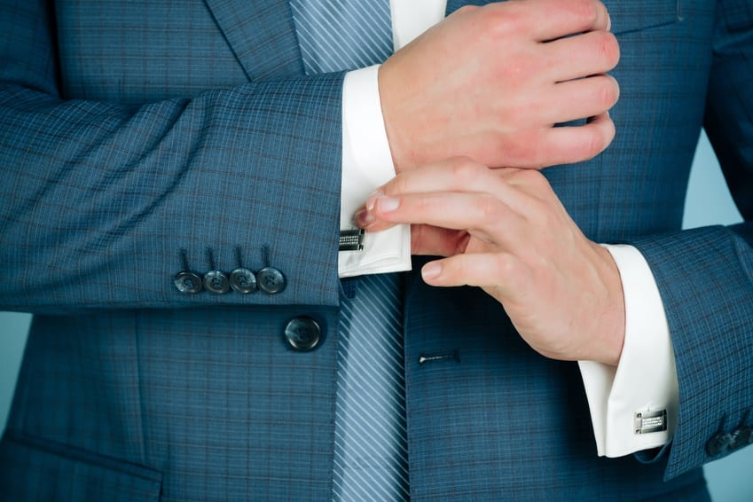 Man fixing stylish cufflinks on white shirt cuffs sleeves custom suit