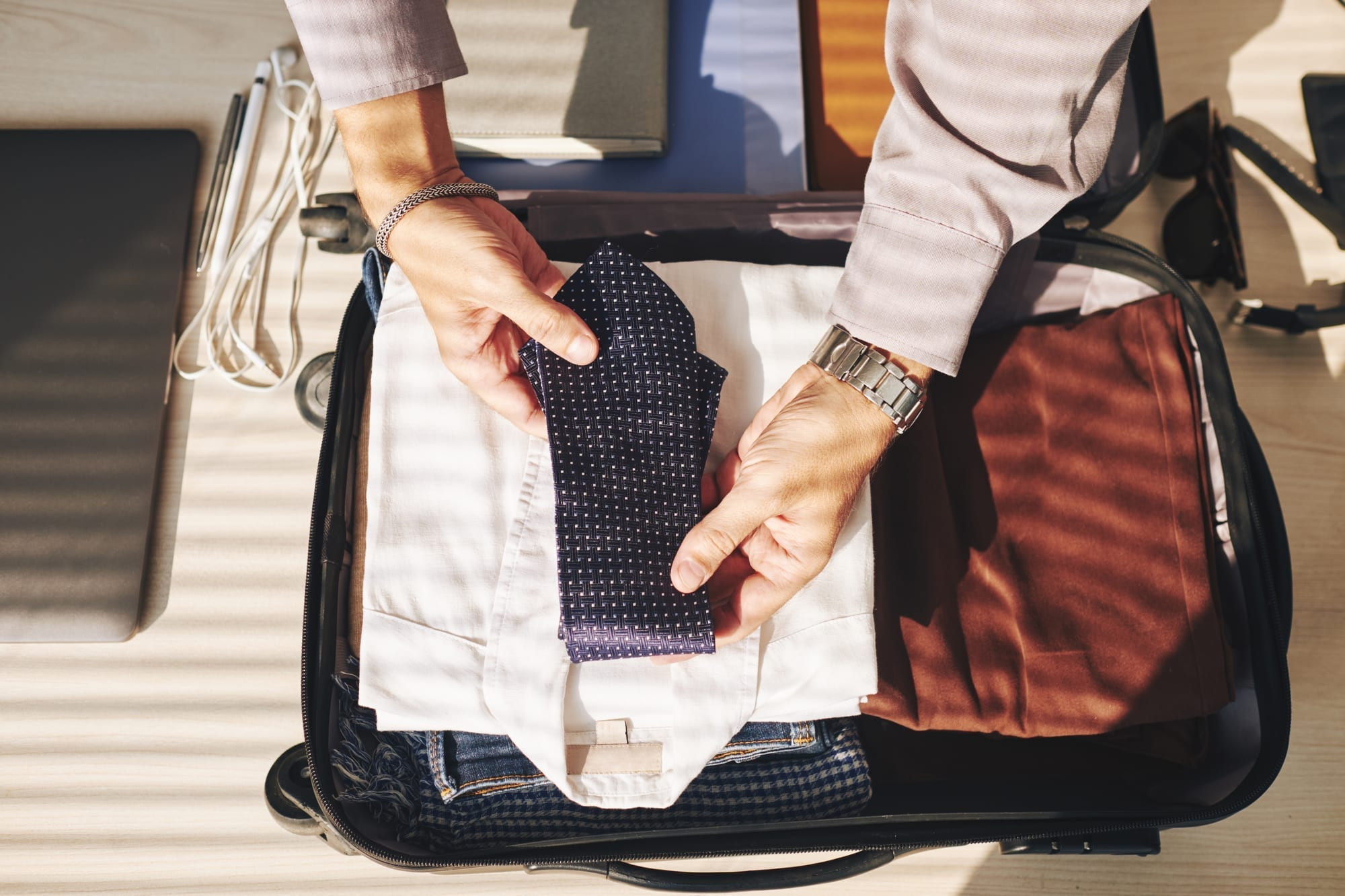 Businessman packing professional clothing wardrobe in suitcase for business trip