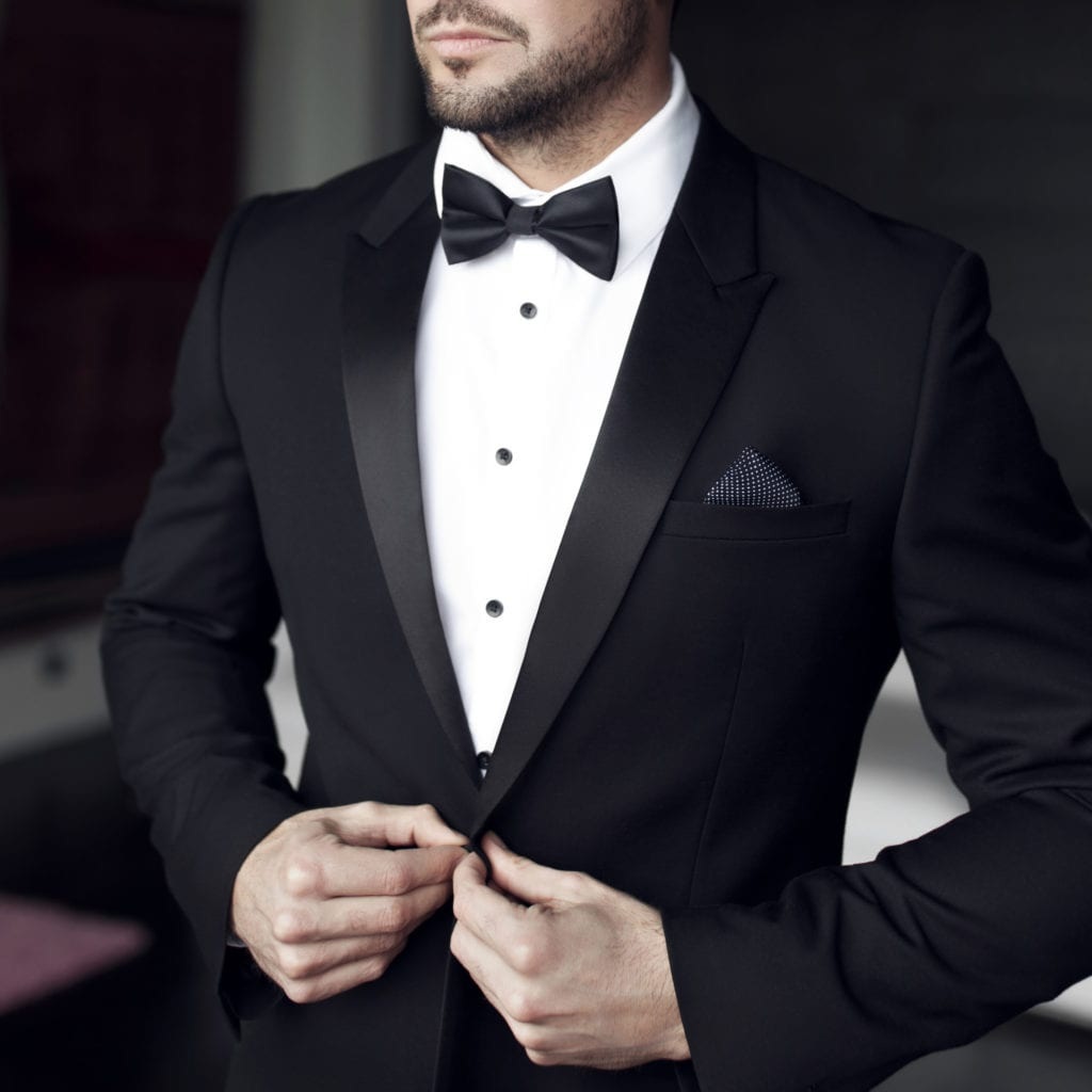 Man in tuxedo and bow tie showing black tie dress code